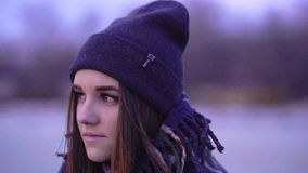 SLOW MOTION: Portrait of a young beautiful frozen girl in a sports hat and a warm plaid in the morning. Before the sunrise of the autumn sun stock footage