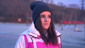 Slow motion: portrait of a young beautiful girl in a sports hat and jacket in the morning. In the light of the morning rising autumn sun stock footage