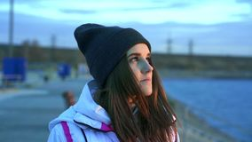 SLOW MOTION: Portrait of a young beautiful girl in a sports hat and jacket in the morning stock video footage