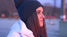 SLOW MOTION: Portrait of a young beautiful girl in a sports hat and jacket in the morning in the light of the morning. Rising autumn sun stock video footage