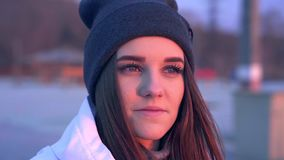Slow motion: portrait of a young beautiful girl in a sports hat and jacket in the morning in the light of the morning. Rising autumn sun stock footage