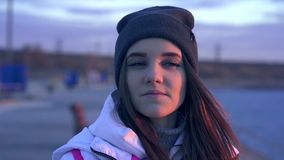 Slow motion: portrait of a young beautiful girl in a sports hat and jacket in the morning. In the light of the morning rising autumn sun stock video footage