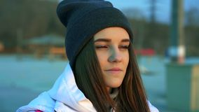 SLOW MOTION: Portrait of a young beautiful girl in a sports hat and jacket in the morning stock footage