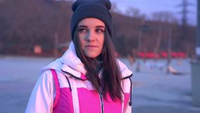 Slow motion: portrait of a young beautiful girl in a sports hat and jacket in the morning. In the light of the morning rising autumn sun stock video