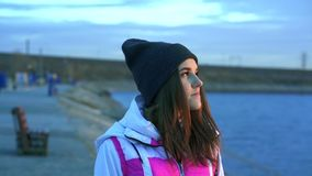 SLOW MOTION: Portrait of a young beautiful girl in a sports hat and jacket in the morning stock video