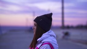 SLOW MOTION: Portrait of a young beautiful girl in the sports hat and jacket in the morning. Before the sunrise of the autumn sun stock video footage