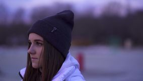 SLOW MOTION: Portrait of a young beautiful girl in the sports hat and jacket in the morning before the sunrise. Of the autumn sun stock video