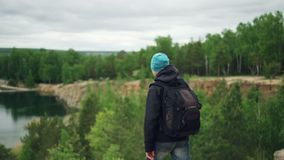 Slow motion portrait of young man tourist with knapsack walking down the hill and watching exciting view under the cliff stock video footage