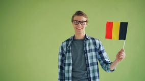 Slow motion portrait of young man waving flag of Germany and smiling stock footage