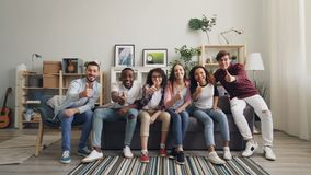 Slow motion portrait of young people running to sofa sitting showing thumbs-up stock video