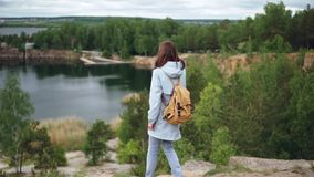 Slow motion portrait of young redhead woman walking to the edge of cliff and watching exciting view of lakes, woods and. Buildings. Beautiful nature, people and stock video