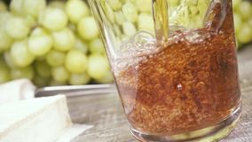 Slow motion pour the wine into a glass and appetizer. Slow motion pour red wine into a glass with drops and splashes near the cheese and grape appetizer stock footage