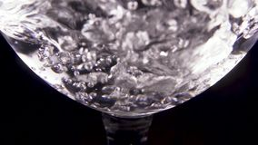 Slow motion pour transparent water into a transparent glass. Slow motion pour the transparent water into a transparent glass with beautiful bubbles stock video