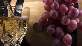 Slow motion pour wine into a crystal glass close up. Slow motion pour white wine into a crystal glass against a bunch of grapes on a wooden wine barrel close up stock footage