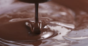 Slow motion of premium dark melted chocolate being poured from spoon in center part of frame. 4k photo Royalty Free Stock Image