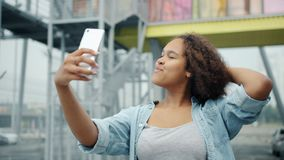 Slow motion of pretty African American woman taking selfie with smartphone outdoors. Posing for camera having fun. People, modern devices and photo concept stock video