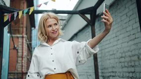 Slow motion of pretty middle aged woman taking selfie with smartphone outdoors stock footage