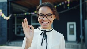 Slow motion of pretty mixed race lady showing OK hand gesture outdoors. Smiling looking at camera alone. Beautiful people, emotions and city concept stock video
