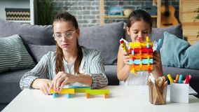 Slow motion of pretty woman playing blocks with cheerful daughter having fun