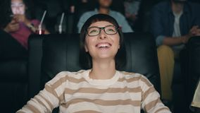 Slow motion of pretty young lady in glasses enjoying film in cinema laughing. Smiling looking at screen with joyful face. People and entertainment concept stock video