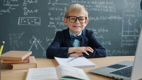 Slow motion of prodigy kid in university classroom at desk with chalkboard in background