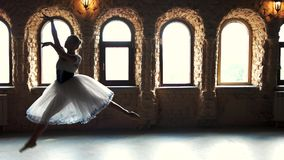 Slow motion professional ballerina dancing in studio. Young graceful ballet girl performing dance on stage at ballet school class stock video footage