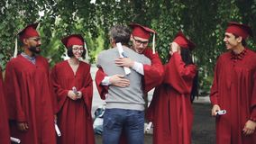 Slow motion of proud university teacher hugging his students and shaking hands, graduating students are standing in line. Slow motion of proud university teacher stock video footage
