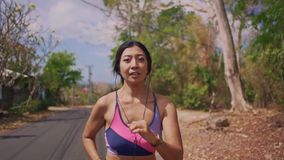 Slow motion pull back gimbal shot of young exotic fit and beautiful Asian Indonesian woman running on trail road jogging. Slow motion pull back gimbal shot in stock footage