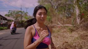 Slow motion pull back gimbal shot of young exotic fit and beautiful Asian Indonesian woman running on trail road jogging. Slow motion pull back gimbal shot in stock video