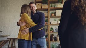 Slow motion of real estate buyers getting keys from housing agent after successful deal, kissing and hugging with. Slow motion of real estate buyers getting keys