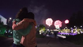 Rear view. Couple hugging against fireworks. Slow motion. Rear view of couple hugging on the background of fireworks in night city