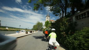 Slow motion - Retired couple cycling on road beside river on holidays stock video footage