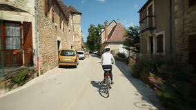 Slow motion - Retired couple cycling on road in village in France stock footage