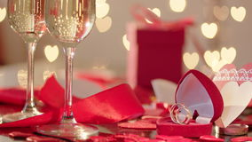 Slow motion rose petals rain falling on wedding rings and glasses filled with champagne stock footage