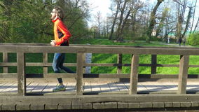 Slow motion of runner crossing a bridge in park. stock video footage