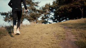 Slow motion runner going uphill to a forest. Low angle back view. Young athlete exploring fall countryside landscapes. Slow motion runner going uphill to a stock video footage