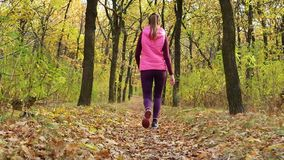 Slow motion Running - woman runner jogging on autumn forest path. Fit female sport fitness model athlete trail running training. Runner girl in sportswear stock video footage