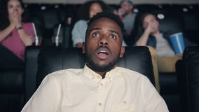 Slow motion of scared African American man watching horror film in cinema. Opening mouth and eyes sitting in dark hall. Youth and emotions concept stock video