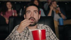 Slow motion of scared guy eating popcorn watching shocking movie in cinema stock footage
