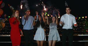 Asian and Caucasian people in roof top party. Slow motion scene of Caucasian man singing song, Asian man playing guitar, Asian and Caucasian women dancing and