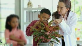 Science teacher teach Asian students in laboratory room, boy look through microscope. stock video