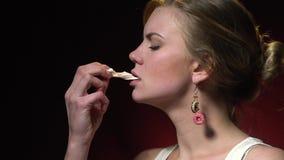 Slow-motion schietende blonde in dat eet heemst op een donkerrode achtergrond stock video