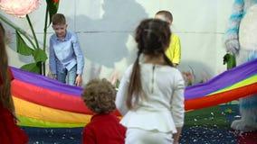 Slow motion of schoolkids running under rainbow cloth at entertainment center.