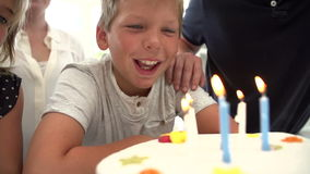 Slow Motion Sequence Of Boy Blowing Out Candles On Cake