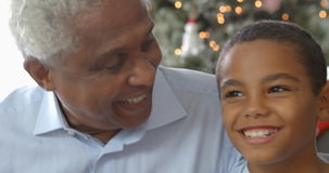 Slow motion sequence of boy sitting on sofa with father and grandfather at Christmas time