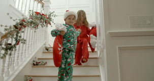 Slow motion sequence of brother and sister wearing pajamas running down stairs holding Christmas stocking filled with gifts stock footage