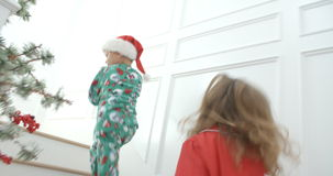 Slow motion sequence of brother and sister wearing pajamas running up stairs on Christmas Eve - view from behind