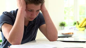 Slow Motion Sequence Of Depressed Boy Studying At Home Stock Image