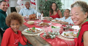 Slow motion sequence of family with grandparents sitting around table and enjoying Christmas meal - looking at camera
