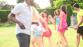 Slow Motion Sequence Of Friends Playing Football In Garden Royalty Free Stock Images